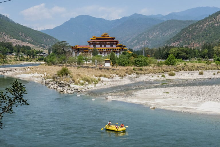 Tourists raft through the river near a Bhutanese temple
