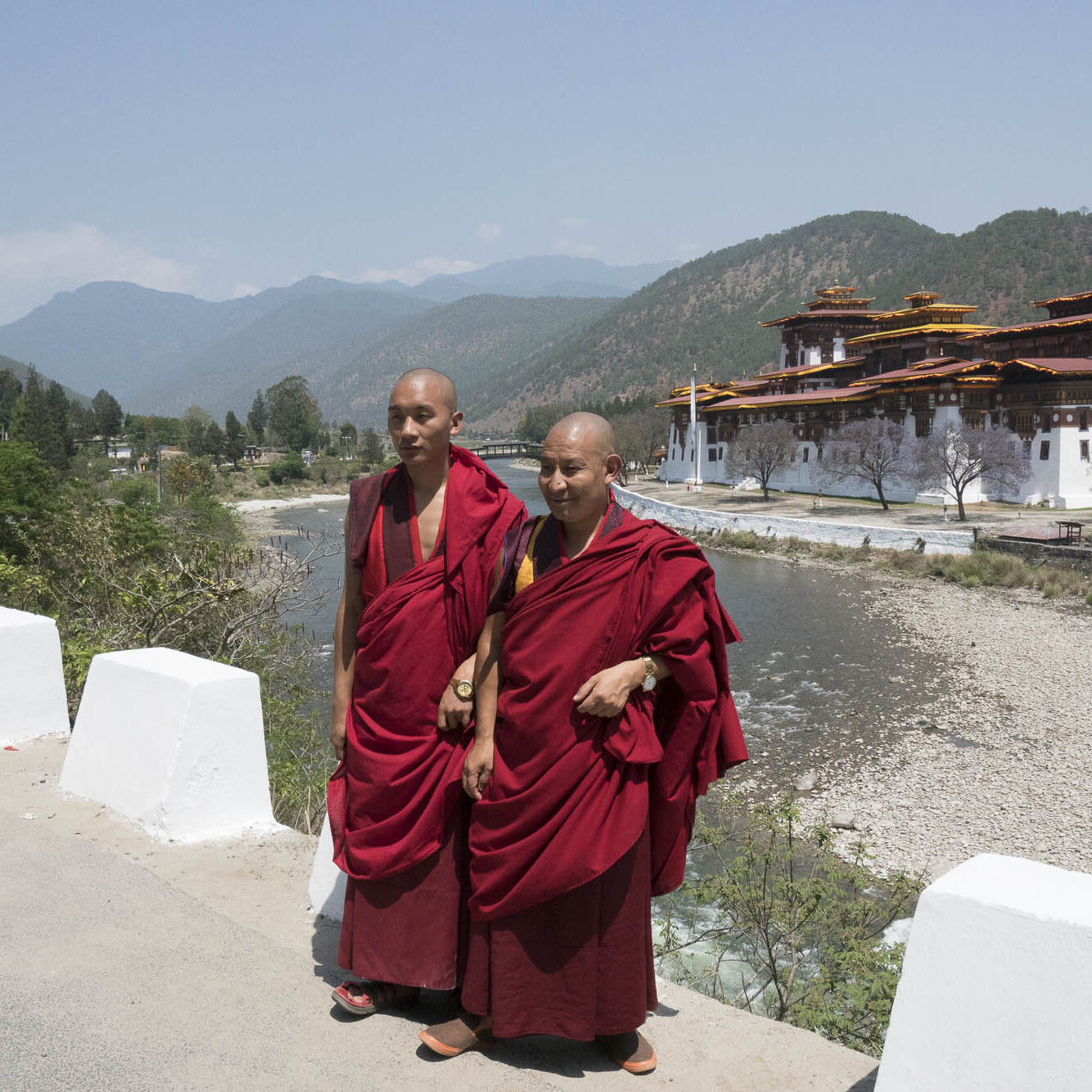 Two Bhutanese monks pose for photos in front of a temple