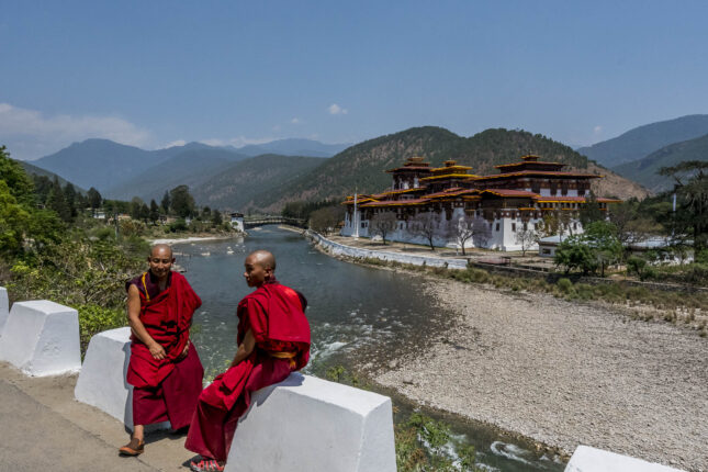Two Bhutanese monks in front of a temple